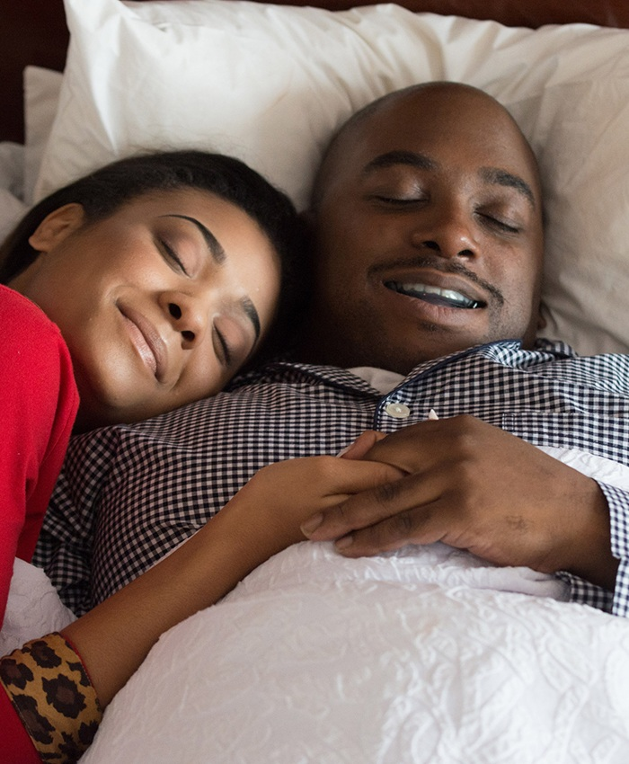 Man with sleep apnea oral appliance and his wife sleeping soundly