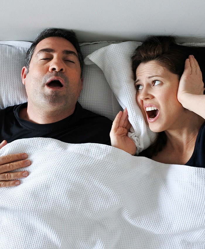 Frustrated woman covering her ears in bed with snoring man